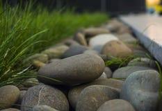 stenen op de grens met groen gras royalty-vrije stock foto's
