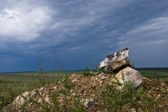Stenen op de heuvel onder de stormachtige hemel Stock Afbeelding