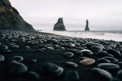 Stenen op een zwart strand in Icelandn Stock Afbeelding