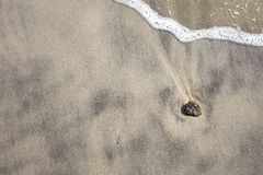 Stenen på stranden med vågen av havet Royaltyfria Foton