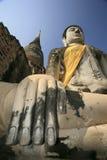 Stenen räcker av Buddha täckte vid orange tyg från tempelet av Wat Yai Chai Mongkol i Ayutthaya, Thailand. Arkivfoto