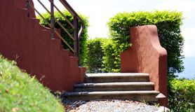 Stenen som fotvandrar banavägen i bergen med trappa till himmel, och himmel med grönt gräs och sörjer träd Royaltyfri Fotografi