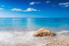 Stenen som tvättas av vågorna och fartyget, seglar Royaltyfri Bild