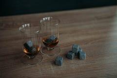 Stenen voor het koelen van whisky en glases tulup op donkere houten achtergrond Stock Foto