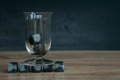 Stenen voor het koelen van whisky en glases tulup op donkere houten achtergrond Royalty-vrije Stock Afbeeldingen