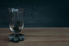 Stenen voor het koelen van whisky en glases tulup op donkere houten achtergrond Stock Fotografie