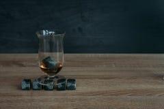 Stenen voor het koelen van whisky en glases tulup op donkere houten achtergrond Royalty-vrije Stock Afbeelding