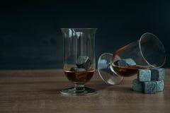 Stenen voor het koelen van whisky en glases tulup op donkere houten achtergrond Royalty-vrije Stock Foto