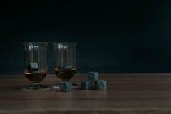 Stenen voor het koelen van whisky en glases tulup op donkere houten achtergrond Royalty-vrije Stock Foto's