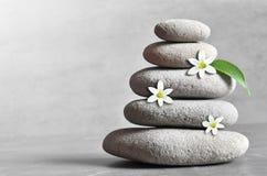 Stenenpiramide met een witte bloem op grijs achtergrond en blad Stock Afbeelding