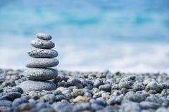 Stenenpiramide op kiezelsteenstrand die kuuroordconcept met onduidelijk beeld overzeese achtergrond symboliseren Royalty-vrije Stock Afbeeldingen