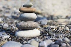 Stenenpiramide op zand die zen, harmonie, saldo symboliseren royalty-vrije stock afbeelding