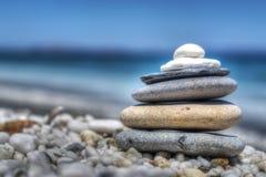 Stenenstapel op witte kiezelstenen door de kust Stock Afbeeldingen