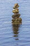 Stenenstapel in water met bezinning Stock Foto's