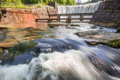 Stenfördämningen skapar en bergvattenfall Arkivfoton