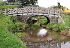 Stenfotbro över den Brecon och Monmouthshire kanalen i södra Wales med narrowboat arkivfoton
