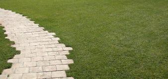 Stenhällträdgård med gräsgräsmatta Arkivbilder