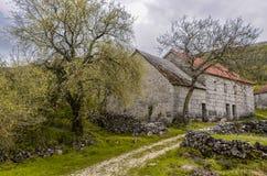 Stenhus i Rosnjace, en liten by i sydvästliga Bosnien och Hercegovina nedanför berget Zavelim Arkivfoton