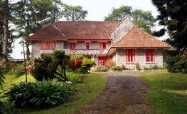Stenhus och trädgård Arkivbild