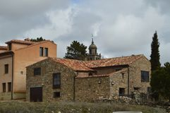 Stenhus på överkanten kan du se det Klocka tornet av domkyrkan i byn av Medinaceli Arkitektur historia, lopp royaltyfri foto