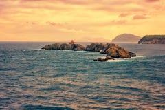 Stenig ö Greben med fyren i Adriatiskt havet, solnedgångseascape, Dubrovnik, Kroatien arkivbilder