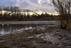 Stenig bank av Obet River på bakgrunden av bron arkivbild