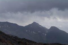 Stenig blast och moln ovanför dem, sikt från lutningen av Elbrus, norr Kaukasus, Ryssland Royaltyfria Foton