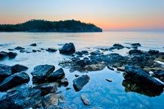 Stenig botten av havet och soluppgången Royaltyfri Bild