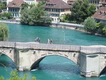 Stenig bro över den rena alpina Aare floden i stad av Bern Arkivfoto