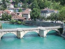 Stenig bro över den rena alpina Aare floden i stad av Bern Royaltyfri Foto
