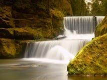Stenig dammbyggnad på den lilla bergfloden Strömmen flödar över kvarter och gör mjölkaktigt vatten Arkivbilder