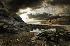 stenig dramatisk liggande för strand arkivfoto