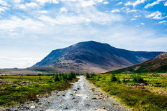 Stenig grusbana som leder till berget under moln och himmel Royaltyfri Bild