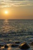 Stenig havkust på den reflekterade solnedgången Arkivfoto