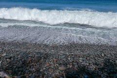 Stenig havkust som tvättas av havsbränningen Vågor som bryter på stenblock på kust Vågor vänder in i ett havsskum arkivbild