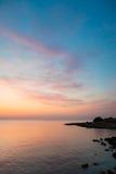 Stenig havskust för soluppgång Arkivfoton