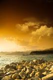 Stenig havskust och dramatisk himmel på solnedgången Royaltyfri Fotografi