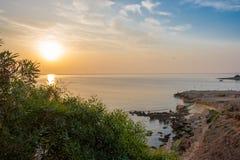 Stenig havskust på soluppgång Arkivfoto