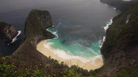 Stenig klippa med stranden i havet Karang Dawa arkivfilmer