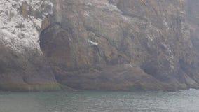 Stenig klippaframsida med vågor som slår mot den arkivfilmer