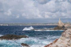 Stenig kust- öppning med avbrottsvågor Royaltyfri Bild