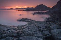Stenig kust av havet på gryning Royaltyfria Bilder