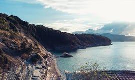 Stenig kust bredvid Ksamil, Saranda, alban Riviera, härlig seascape, solnedgång arkivfoto