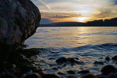 Stenig kust för behållarsolnedgång Royaltyfri Foto