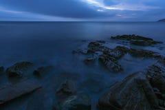 Stenig kust i aftonskymningen Royaltyfria Foton