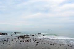 Stenig kust med det dimmiga havet och skyen Fotografering för Bildbyråer