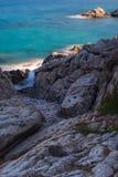 Stenig kust med lövverk in mot smaragdvatten arkivfoto