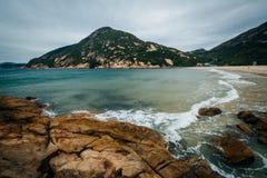 Stenig kust och sikt av det D'Aguilar maximumet, på den Shek nolla-stranden, på Hon royaltyfri bild