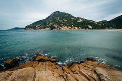 Stenig kust och sikt av det D'Aguilar maximumet, på den Shek nolla-stranden, på Hon royaltyfri fotografi