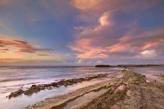 Stenig kust på ön av Curaçao på solnedgången Royaltyfri Fotografi